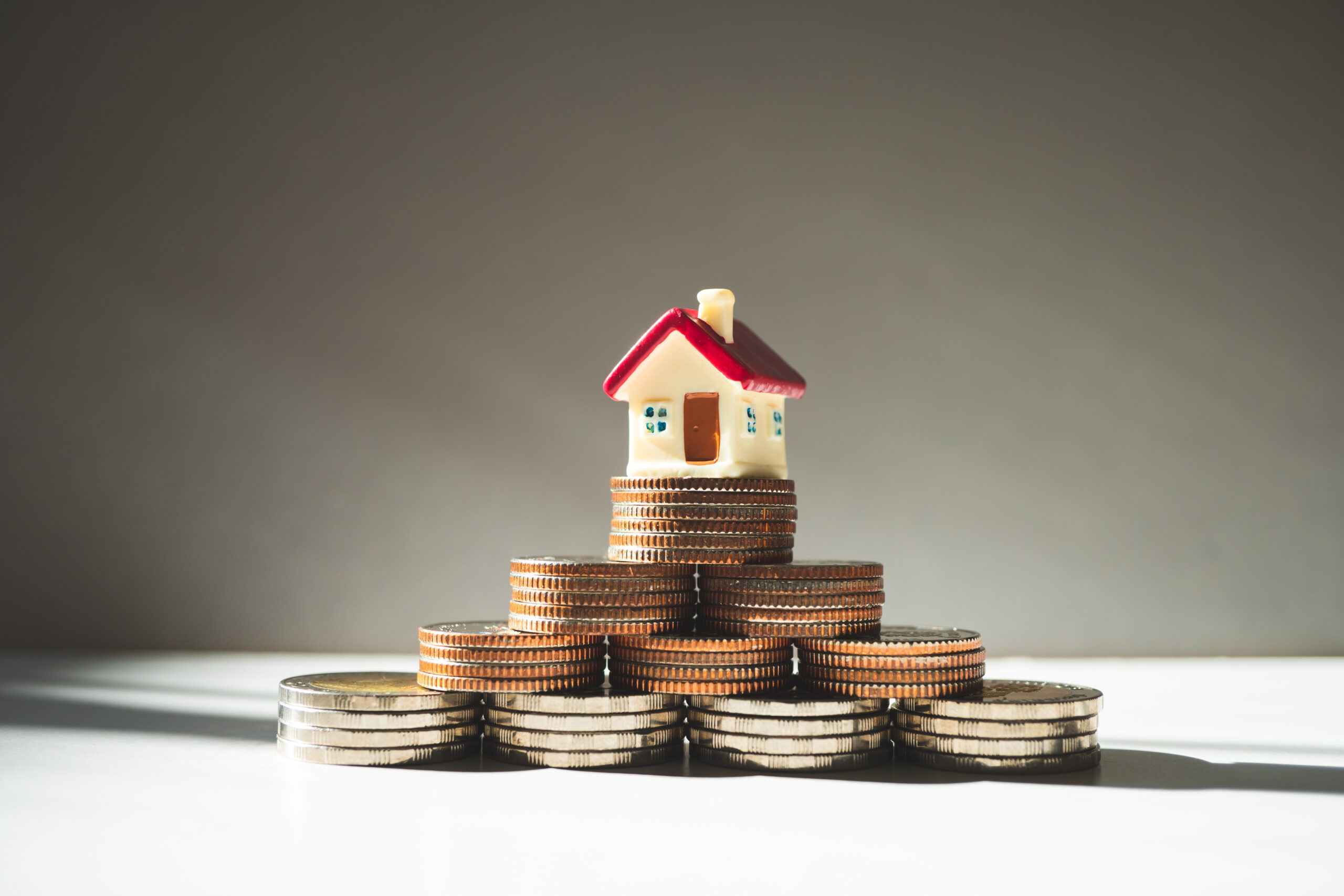 Miniature colorful house on stack coins using as propert